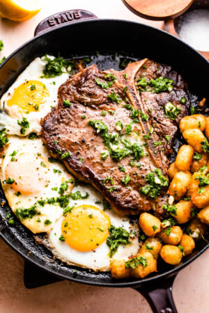 skillet with t-bone steak with over-easy eggs and tater tots arranged around it.