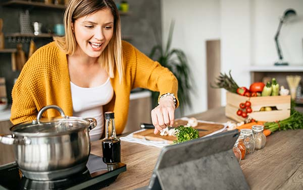 Woman cooking and looking at her tablet for instructions